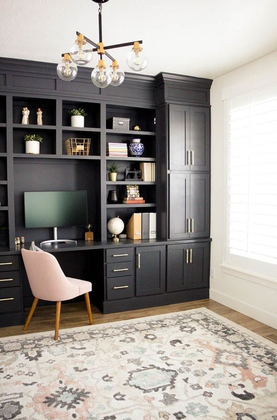 a modern farmhouse home office done with black kitchen cabinets, a blush chair, a retro chandelier and gold touches