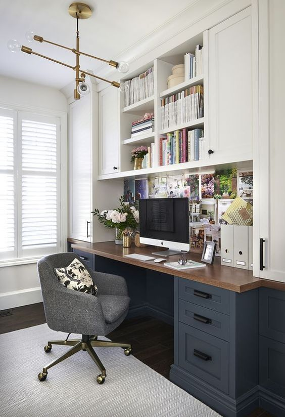 a modern farmhouse home office with two tone kitchen cabinets, a desk with a butcherblock countertop, a grey chair and a vintage chandelier