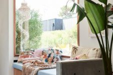 06 a boho space with a corner window for light and a lovely garden view, a daybed with colorful pillows and a statement plant next to it
