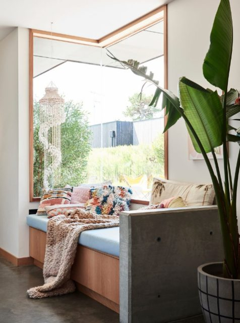 a boho space with a corner window for light and a lovely garden view, a daybed with colorful pillows and a statement plant next to it