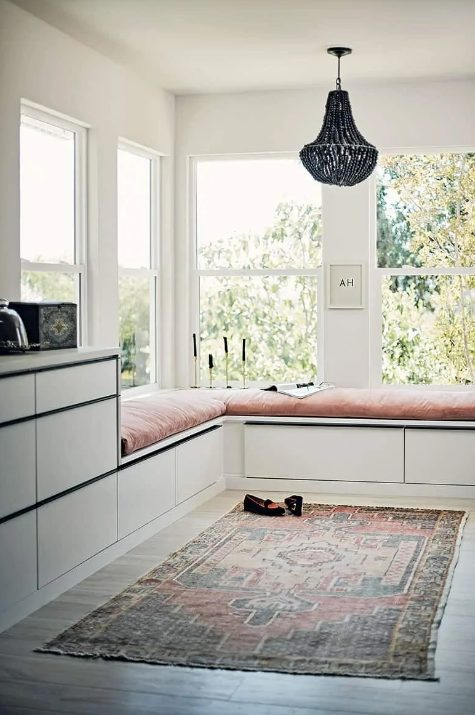 a chic space with corner windows, a large double daybed with storage drawers and more storage around, a boho rug and a wooden bead chandelier
