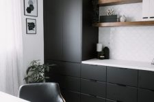 07 a modern home office with sleek black cabinets and a white tile backsplash, floating shelves and a white desk plus a retro chandelier