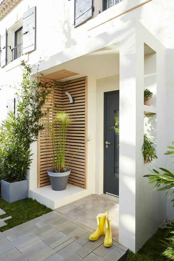 a laconic modern porch with a planked space featuring some potted plants, a black glass door and yellow rubber boots for a fun touch