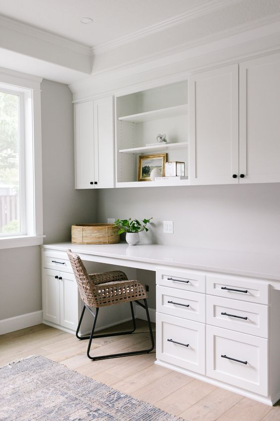 a modern neutral home office with white shaker style cabinets, a desk with lots of storage, a rattan chair and some plants