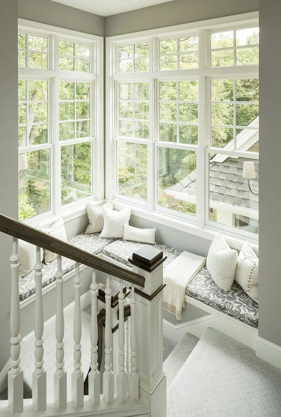 a corner window at the staircase with a large daybed with pillows and a blanket to enjoy a book and a cup of tea with a view