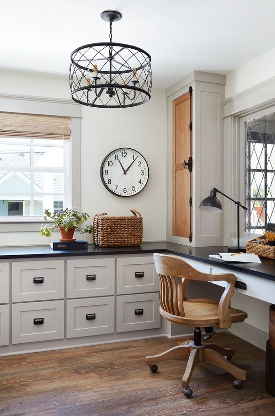 a stylish farmhouse home office done with pretty kitchen cabintery and a built in desk, a wooden chair, a metal chandelier and a basket