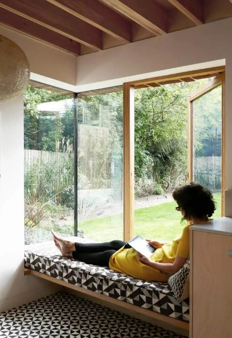 a corner window with a daybed and printed bedding allows natural light, views and even an exit to the garden