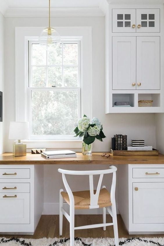 a welcoming white farmhouse home office done with kitchen cabinets and a matching desk, a woven chair and a pendant lamp