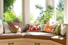 12 a corner window with a windowsill daybed, with drawers for storage and colorful pillows is a lovely space to spend your time here