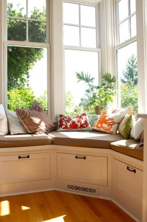 a corner window with a windowsill daybed, with drawers for storage and colorful pillows is a lovely space to spend your time here