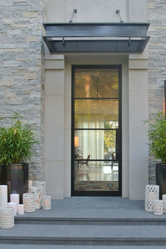 a modern front porch with a creative glass door, greenery in tall black planters and lots of laser cut candleholders and candles on the steps