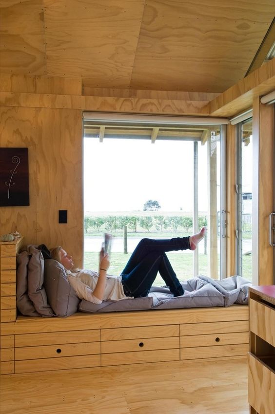 a corner window with a windowsill daybed, with storage drawers is a very cozy and lovely space with cool views and much natural light