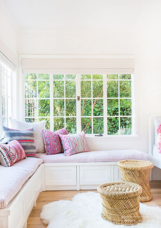 a cozy and inviting nook with a corner window, a corner daybed with colorful pillows and rattan stools is very chic and lovely