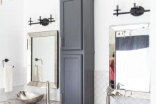 14 a midnight blue bathroom done with various kitchen cabinets and a grey stone countertop, hammered bowl sinks and a vintage chandelier