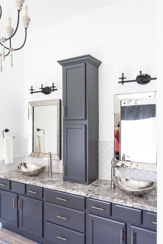 a midnight blue bathroom done with various kitchen cabinets and a grey stone countertop, hammered bowl sinks and a vintage chandelier