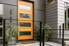 15 a stylish modern entrance with grey walls, a glass insert stained door, grey planters with greenery that features a lot of texture