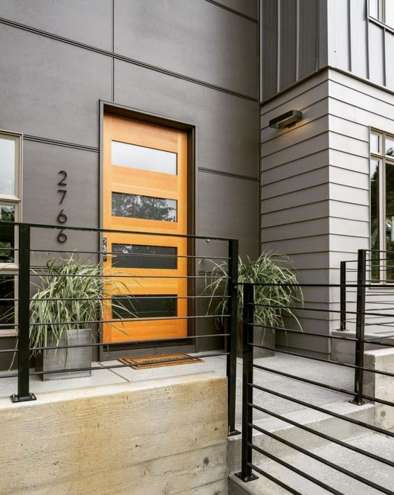 a stylish modern entrance with grey walls, a glass insert stained door, grey planters with greenery that features a lot of texture