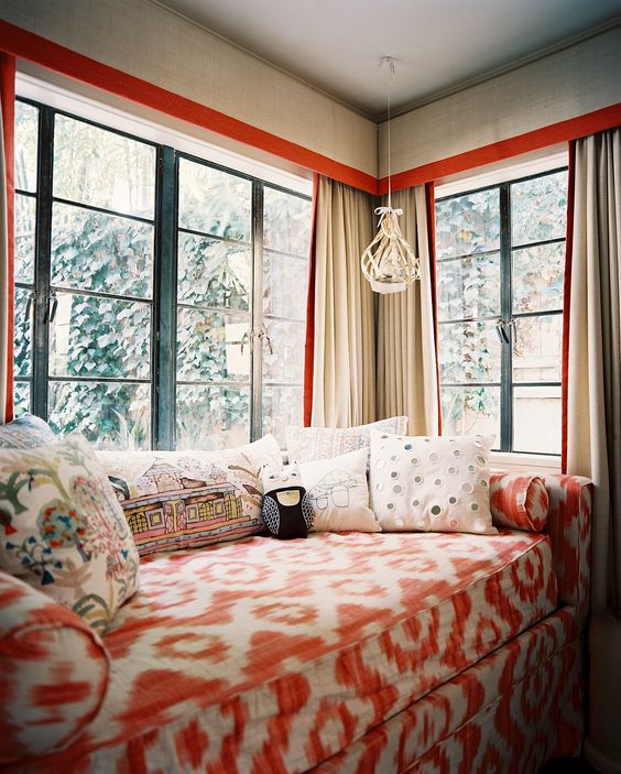 a gorgeous and bright corner space with a corner window, a colorful sofa with lots of pillows just welcomes to stay here