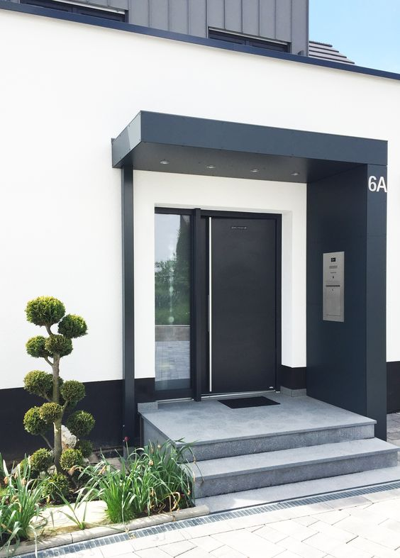 a stylish modern to minimalist porch done with concrete steps, a black door, some grass and a mini trees next to it looks chic