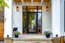 17 a modern and fresh porch with a glass door, bold blue planters with lilac blooms and a hanging chair plus lanterns on the walls
