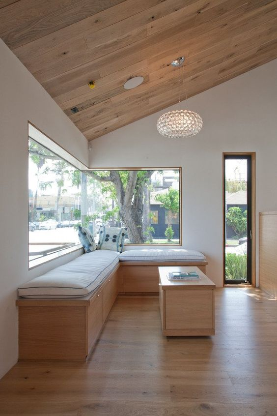 a welcoming modern space with a corner window and a large daybed with upholstery, a crystal chandelier and a coffee table