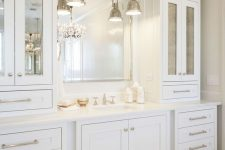 17 an elegant and stylish creamy bathroom made with vintage kitchen cabinets, a mirror in a metallic frame and vintage pendant lamps