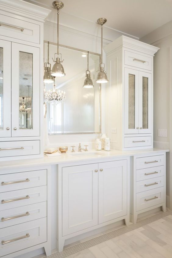 an elegant and stylish creamy bathroom made with vintage kitchen cabinets, a mirror in a metallic frame and vintage pendant lamps