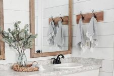 18 a stylish white bathroom with planked walls, a large white vanity made of kitchen cabinets, a grey stone counterop and mirrors in wooden frames