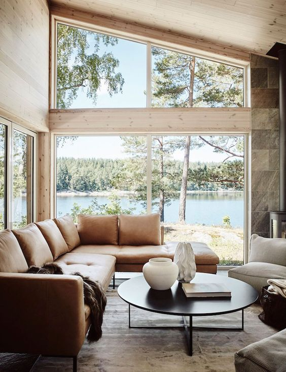 a welcoming contemporary living room with wood clad walls, a large corner window, a leather sofa, a coffee table and a neutral chair