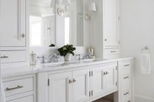 19 a gorgeous master bathroom with creamy shaker style cabinets from the kitchen, a double mirror and sink, sconces and a chic floor
