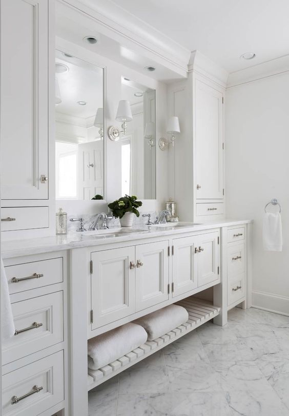 a gorgeous master bathroom with creamy shaker style cabinets from the kitchen, a double mirror and sink, sconces and a chic floor