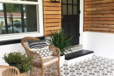 a modern porch clad with pretty star-patterned tiles, with rattan chairs, potted greenery and a black door and steps is a chic idea