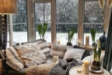 20 a Scandinavian nook with a corner window, a daybed with lots of pillows and blankets, candles and candle lanterns