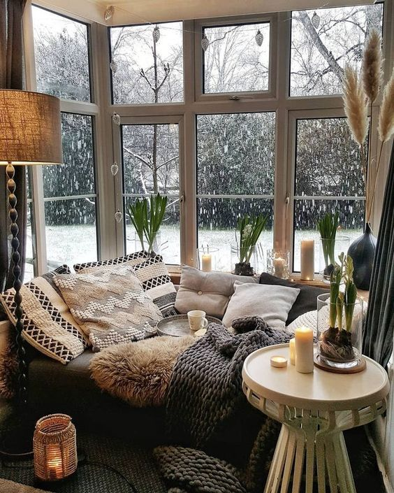 a Scandinavian nook with a corner window, a daybed with lots of pillows and blankets, candles and candle lanterns