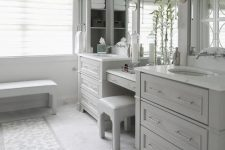 20 a beautiful dove grey bathroom done with kitchen cabinets, large mirrors, a bench and a stool and sconces