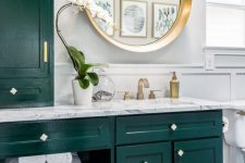 21 a bright and chic bathroom with dark green kitchen cabinetry, a penny tile floor, some gold touches for more chic