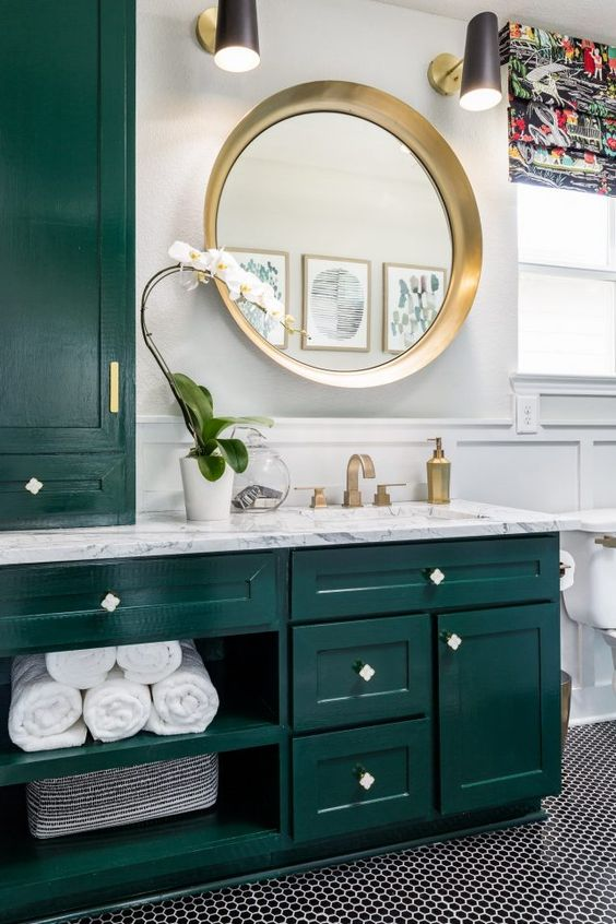 a bright and chic bathroom with dark green kitchen cabinetry, a penny tile floor, some gold touches for more chic