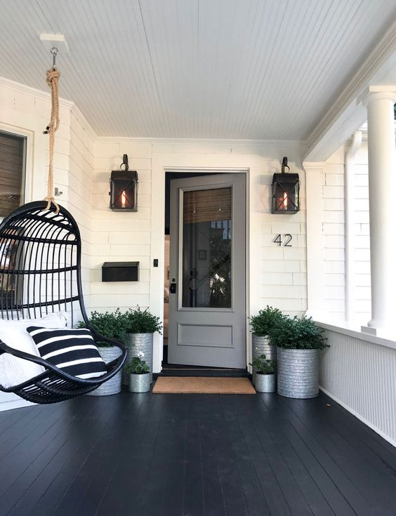 a modern porch with a black planked floor, a black pendant egg-shaped chair, lots of greenery in tin cans and lanterns on the wall