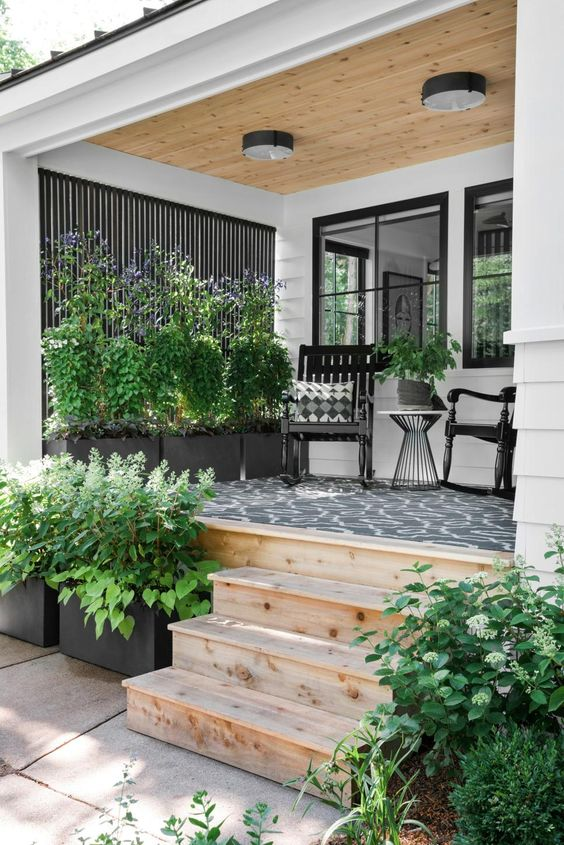 a modern porch with a cool printed rug, potted greenery, black rockers and a coffee table plus ceiling lamps is amazing