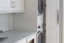 22 a neutral laundry with shaker style kitchen cabinets, neutral stone countertops and much storage space is lovely