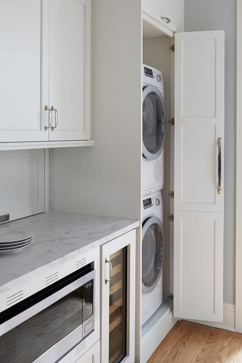 a neutral laundry with shaker style kitchen cabinets, neutral stone countertops and much storage space is lovely