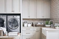 23 a gorgeous dove grey laundry room done with shaker style kitchen cabinets, a brick wall, potted plants and a cool tile floor