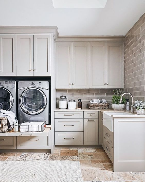 a gorgeous dove grey laundry room done with shaker style kitchen cabinets, a brick wall, potted plants and a cool tile floor
