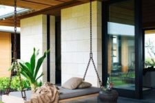 23 a modern porch with a swinging daybed on chains and a carved wooden side table feels and looks very zen-like