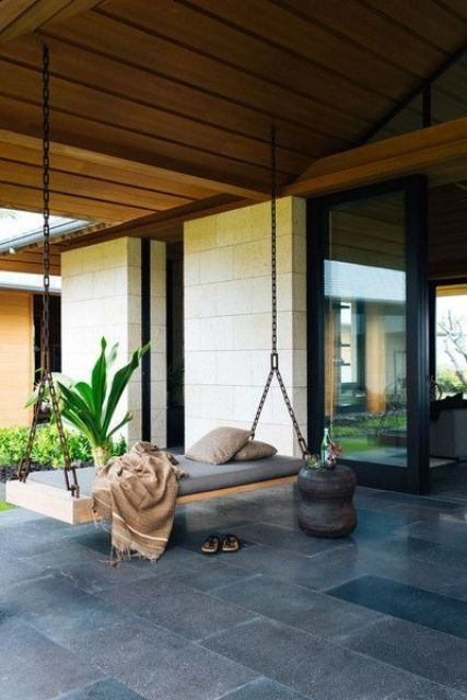 a modern porch with a swinging daybed on chains and a carved wooden side table feels and looks very zen-like