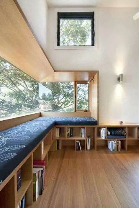 a modern reading nook with a corner window, a large daybed with built in bookshelves is a very welcoming and cool space to stay
