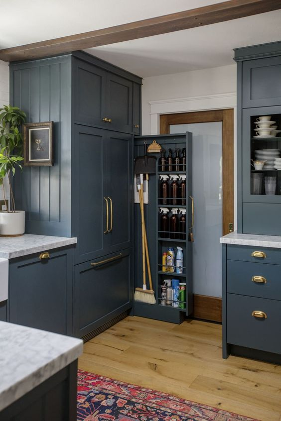 a chic laundry with graphite grey shaker kitchen cabinets, wooden beams and a lovely printed rug