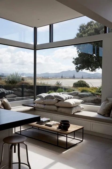 a minimalist space with a corner window for a gorgeous view and much natural light, a daybed with pillows and a minimalist coffee table