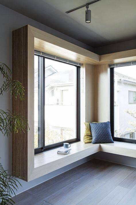 a minimalist corner window space with extended frames, a windowsill seat with pillows and books and coffee is a great space to be