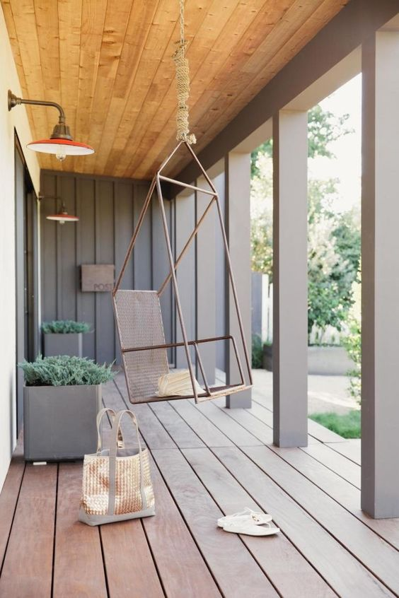 a modern porch with pillars, a planked wooden floor, a hanging metal chair, metal planters with greenery looks ultimate chic